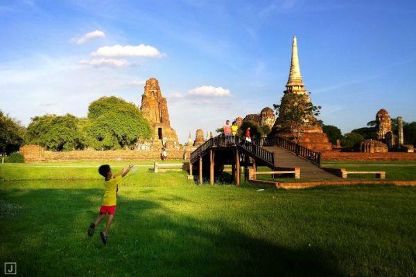 เด็กกำลังวิ่งเล่นอยู่สนามหญ้า ข้าง ๆ วัดพระมหาธาตุ